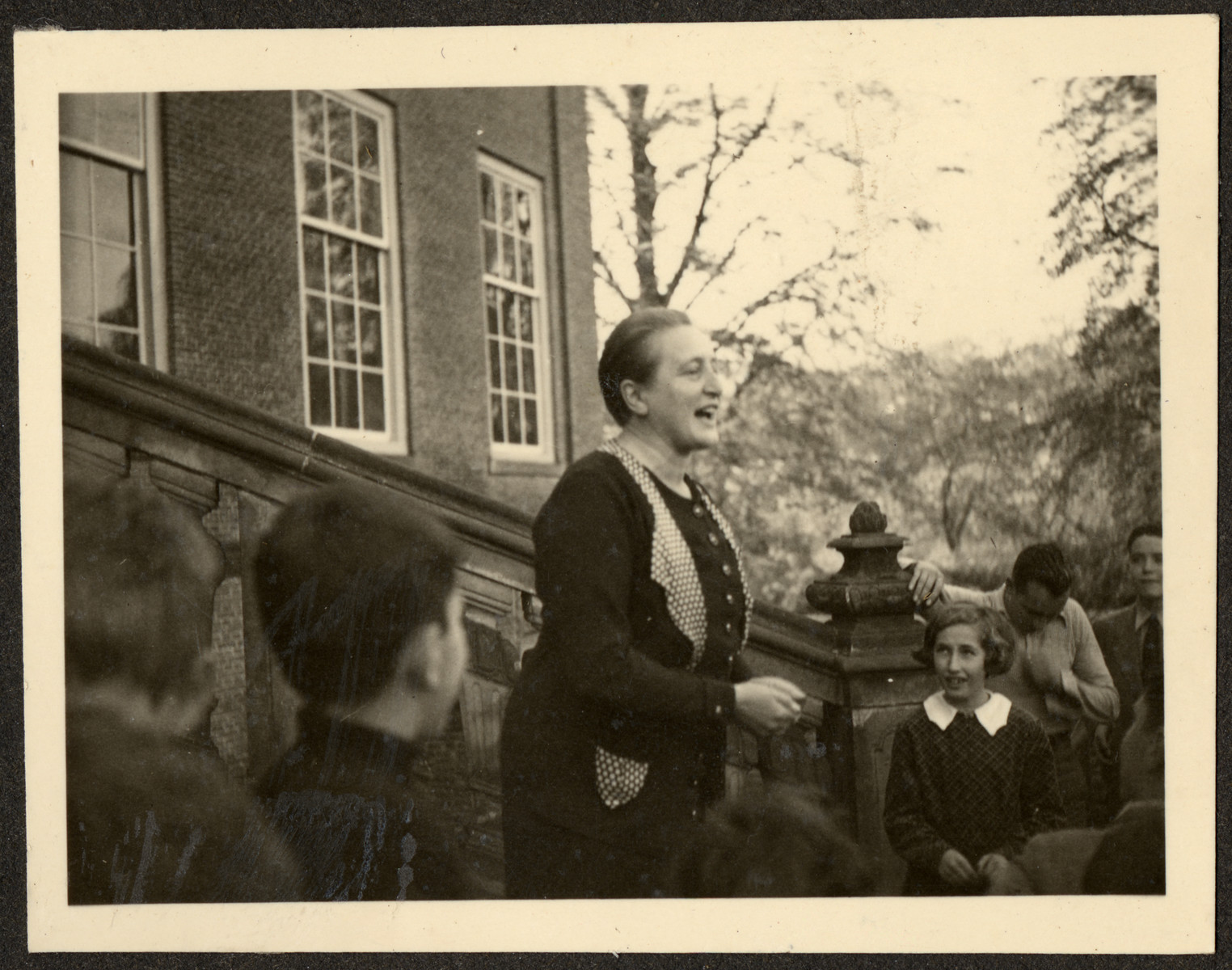 A teacher leads an activity for students, many of them German Jewish refugees, on the steps of a Quaker boarding school in Eerde.