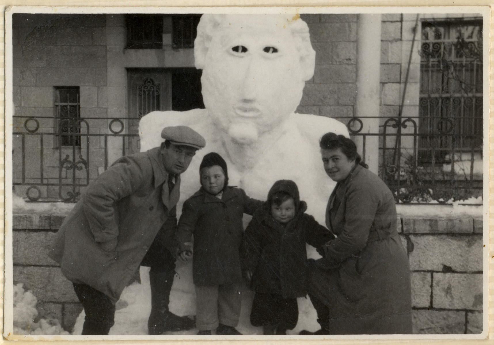 The Kohl family poses in front of a large snow sculpture in the Hofgeismar displaced persons camp.  From left to right are Emil, Miriam, Sam and Dora Kohl.