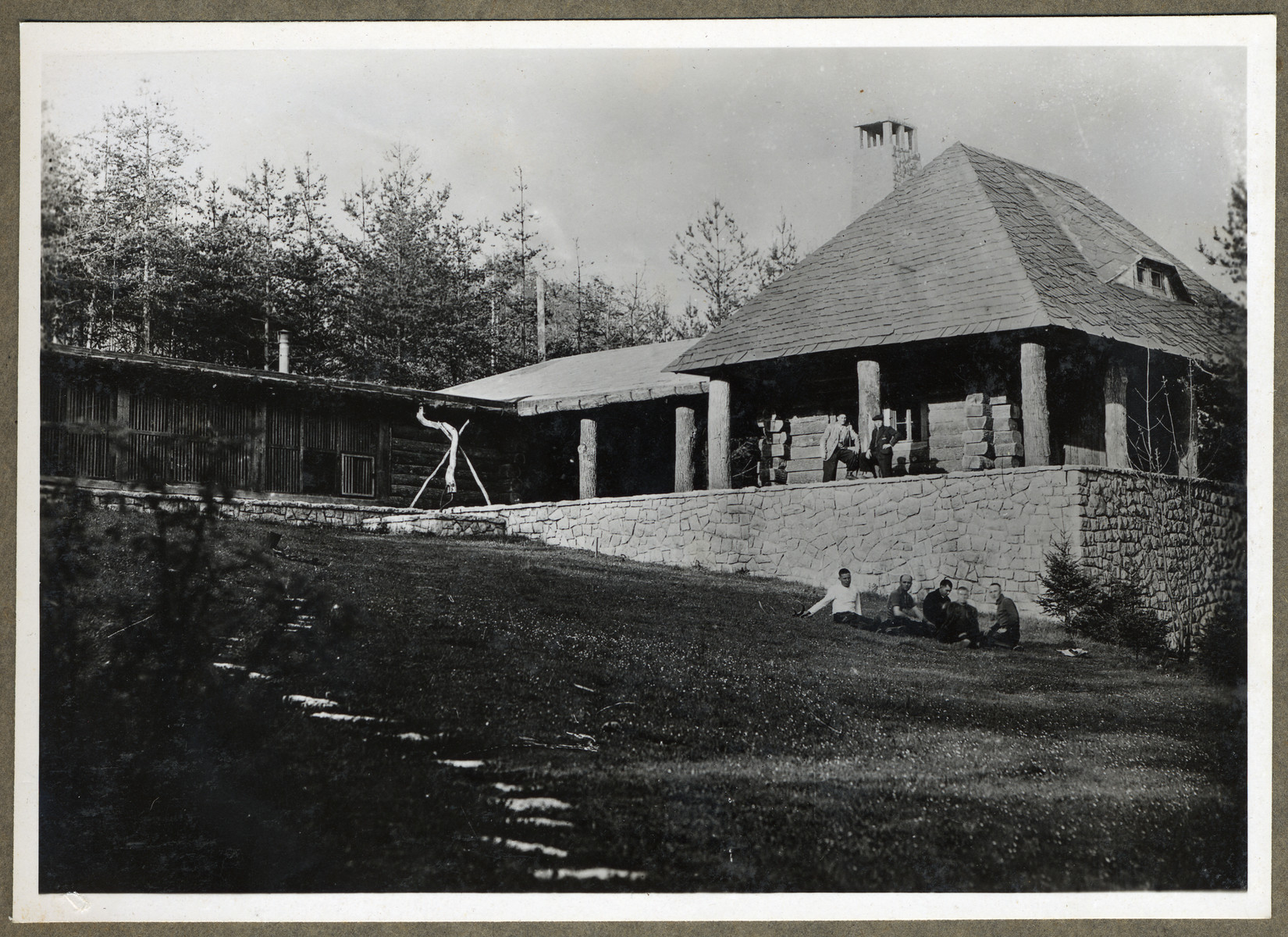 Survivors mingle on the porch and yard of a building [possibly abandoned SS housing] following liberation.