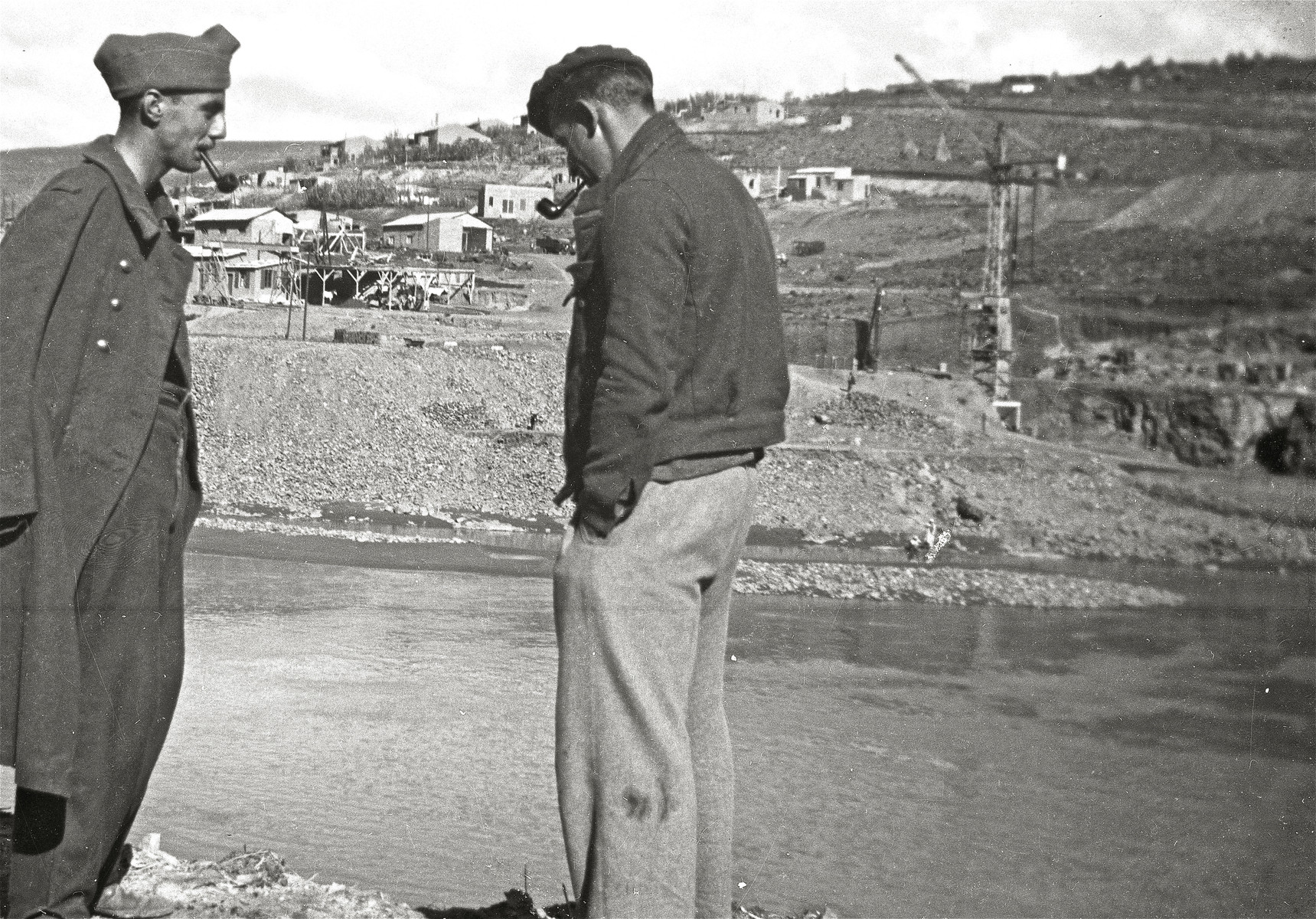 Two prisoners stand by the river and smoke pipes at the Im Fout labor camp in Morocco.  Pictured are Sami Dorra and Rosenthal.