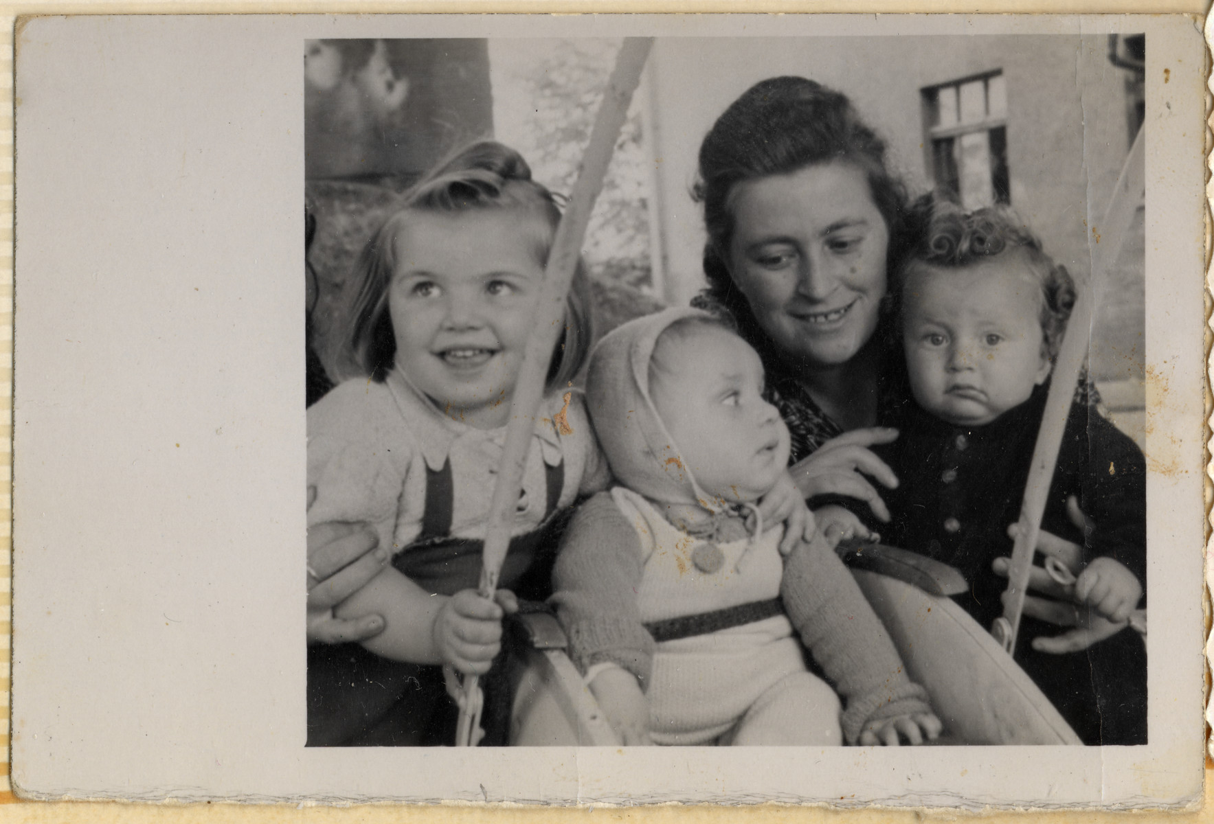 Dora Kohl poses with her two children Miriam and Sam and an unidentified baby in the Hofgeismar displaced persons camp.