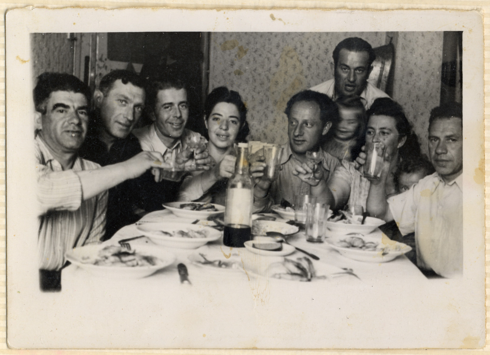 A group of friends gather around a table for a celebration in the Hofgeismar displaced persons camp.  Emil Kohl is standing in the back holding his daughter Miriam.