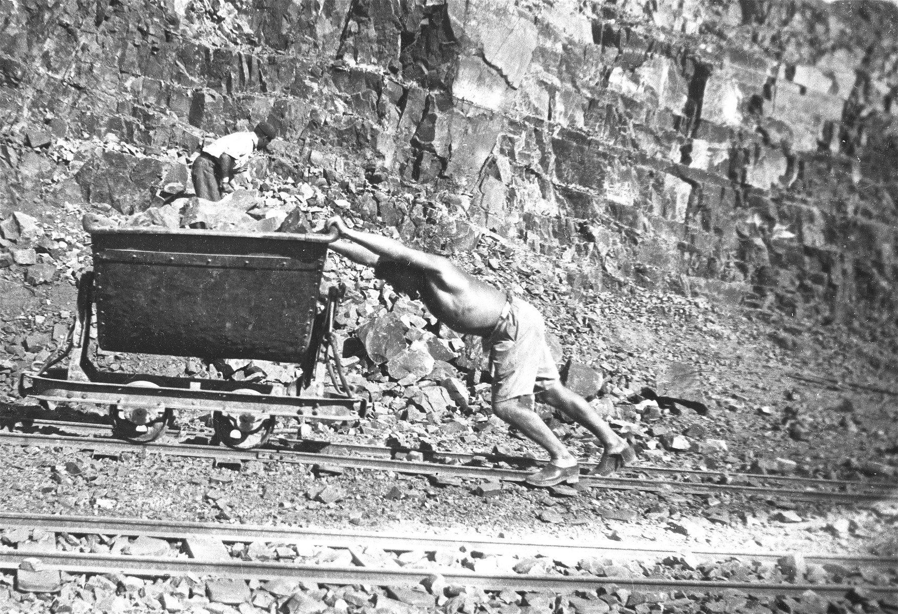 Rosenthal, a German Jewish prisoner, pushes a cart in the stone quarry of the Im Fout labor camp in Morocco.