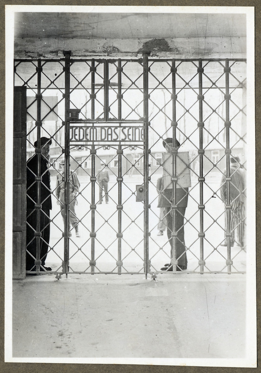 """Survivors stand behind the main gate of the Buchenwald concentration camp with a sign that reads Jedem das Seine, """"To Each What is His.""""  Louis Fynaut  is the man on the front, right side of the picture."""