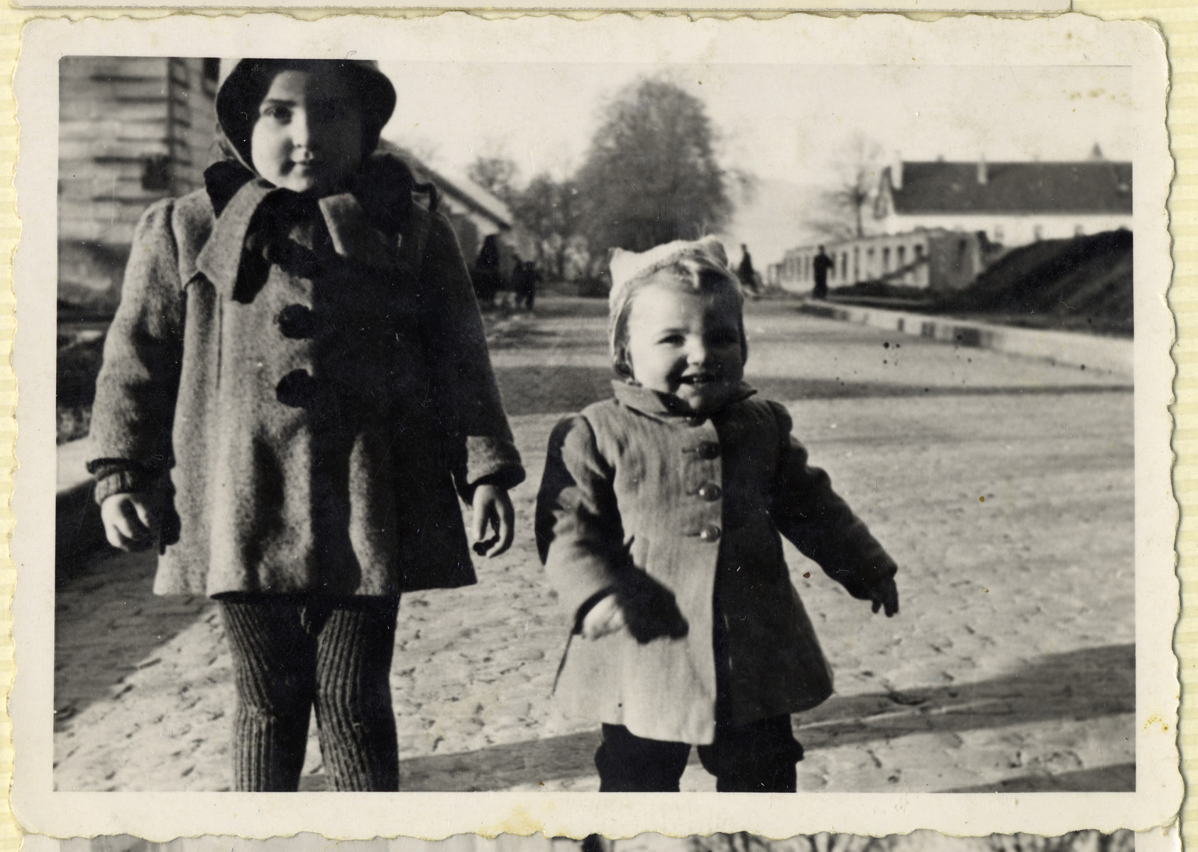 Two young children stand on a street of the Hofgeismar displaced persons camp.  [Pictured possibly are Miriam and Sam Kohl]
