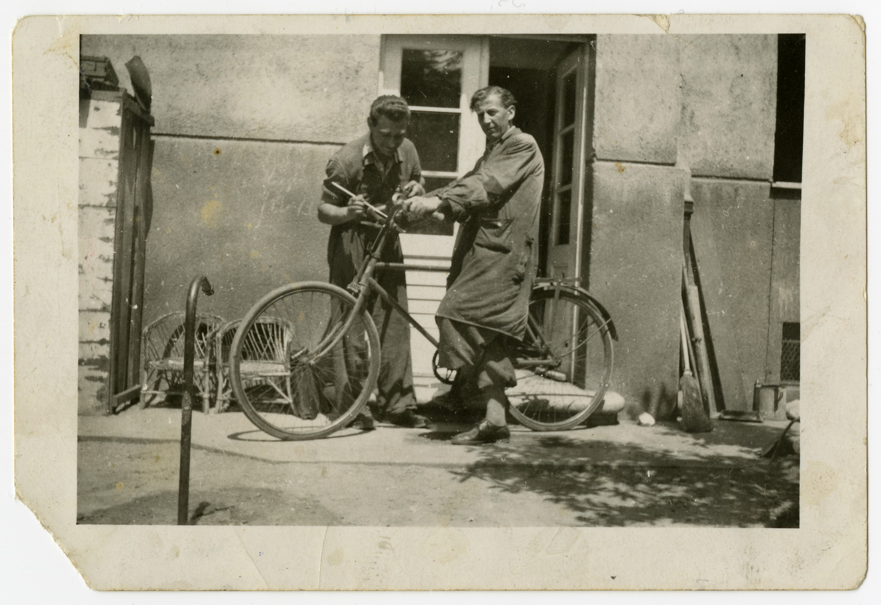 Oscar Kalmar adjusts the bicycle of a friend in prewar Zlate Moravce.
