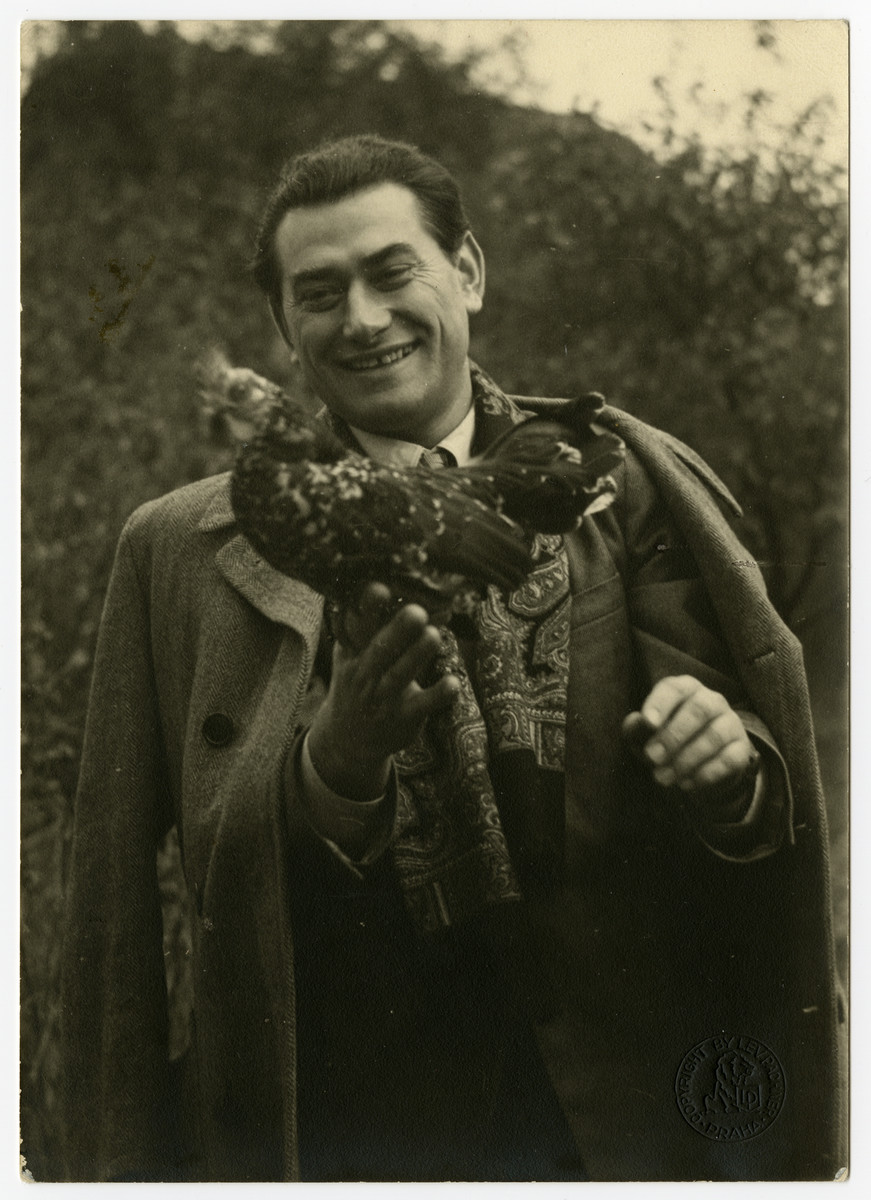 Dr. Oscar Kalmar holds a chicken that he received as payment for dental work in postwar Czechoslovakia.