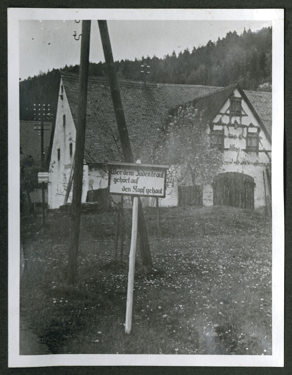 "One photograph from an album of antisemitic signs in Germany.  The sign (in German) reads, ""Wer dem Juden traut gehoert auf den Kopf gehaut.""  [He who trusts the Jews needs a good knock on the head.]"