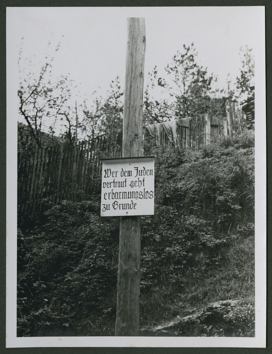 "One photograph from an album of antisemitic signs in Germany.  The sign (in German) reads, ""Wer dem Juden vertraut geht erbarmungslos zu Gruende.""  [He who trusts the Jews perishes.]"