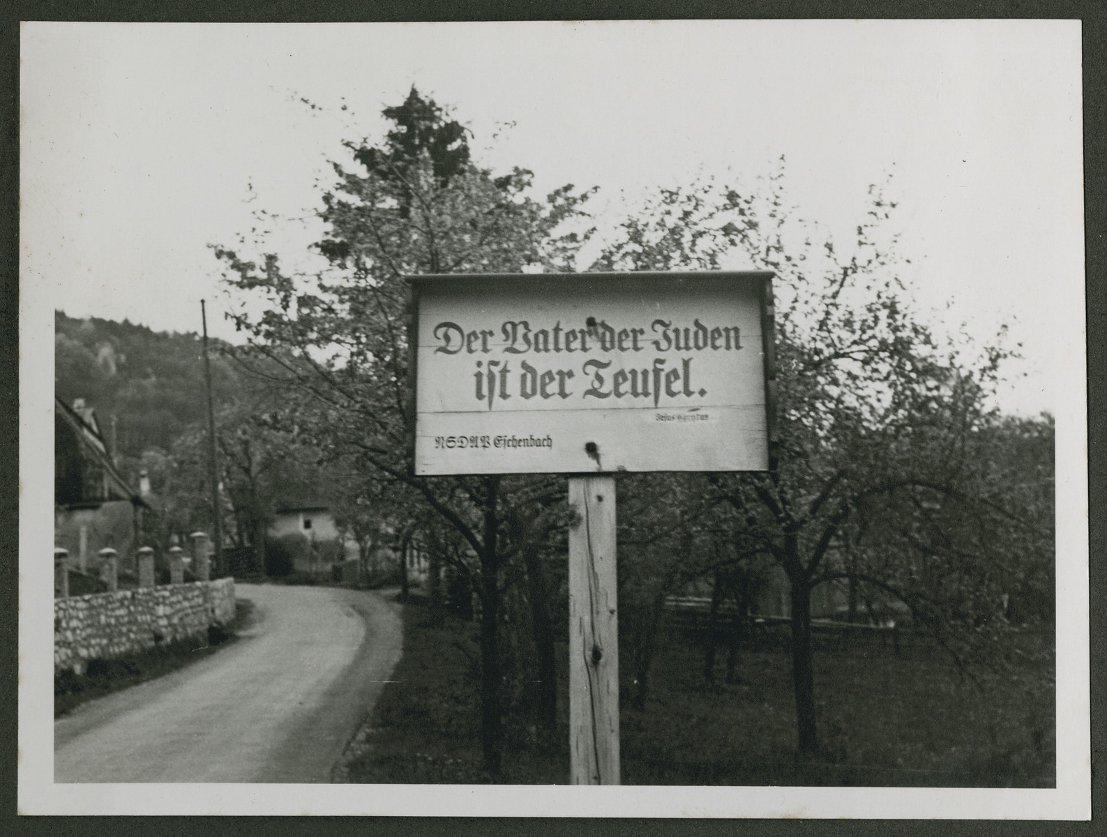 """One photograph from an album of antisemitic signs in Germany.  The sign (in German) reads, """"Der Vater der Juden ist der Teufel.  NSDAP Eichenbach.""""  [The father of the Jew is the devil.]"""