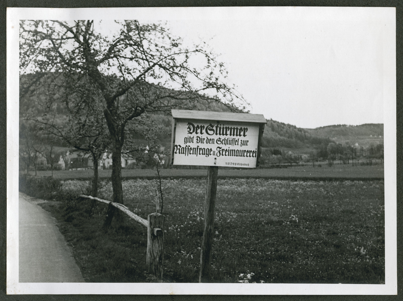 "One photograph from an album of antisemitic signs in Germany.  The sign (in German) reads, ""Der Stuermer gibt Dir den Schluessel zur Rassenfrage und Freimaurerei.  NSDAP Eichenabach."" [Der Stuermer gives you the key to the race question and free masonry.]"
