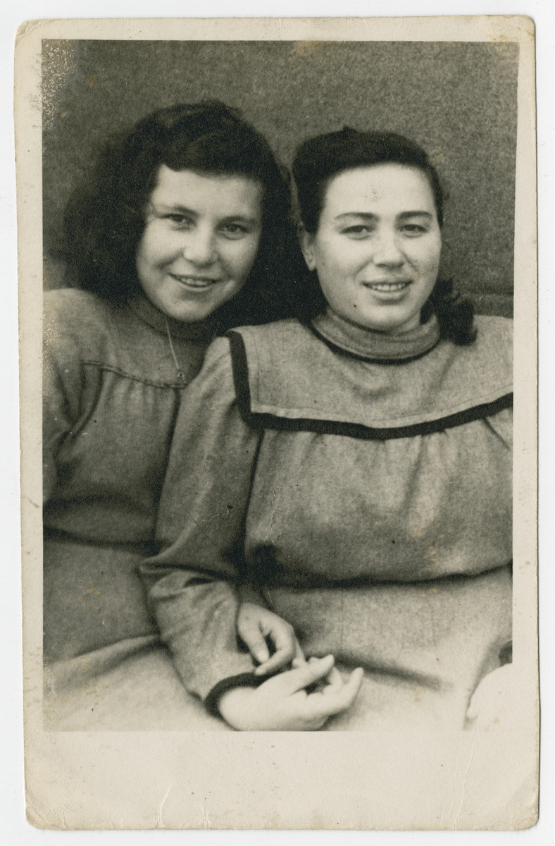 Studio portrait of cousins Malka and Rifka Weiss.    They survived concentration camp and death march together.  Their matching dresses were sewn from a blanket.