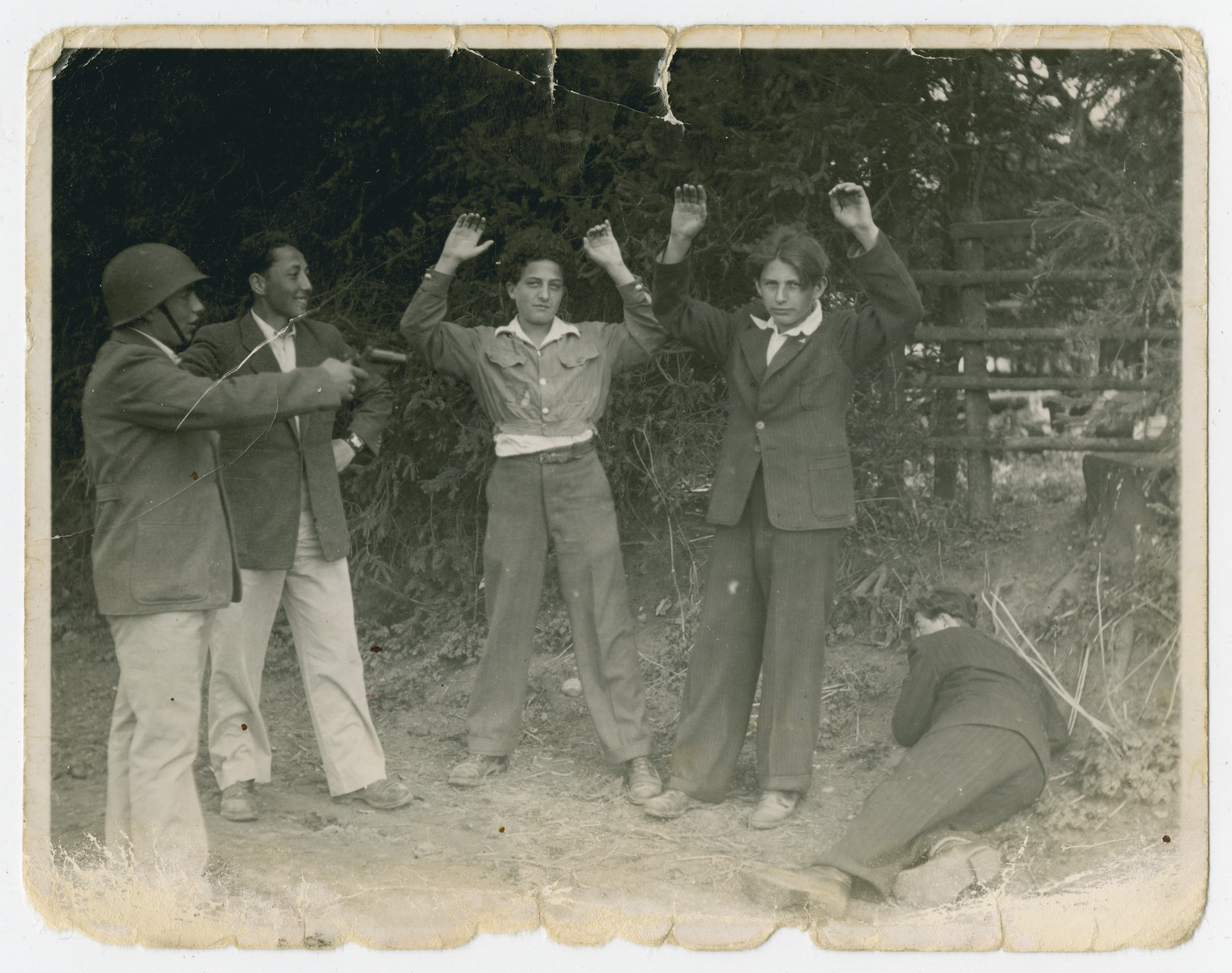 Young survivors play act an arrest.  One of the men is Mordechai Hellman.