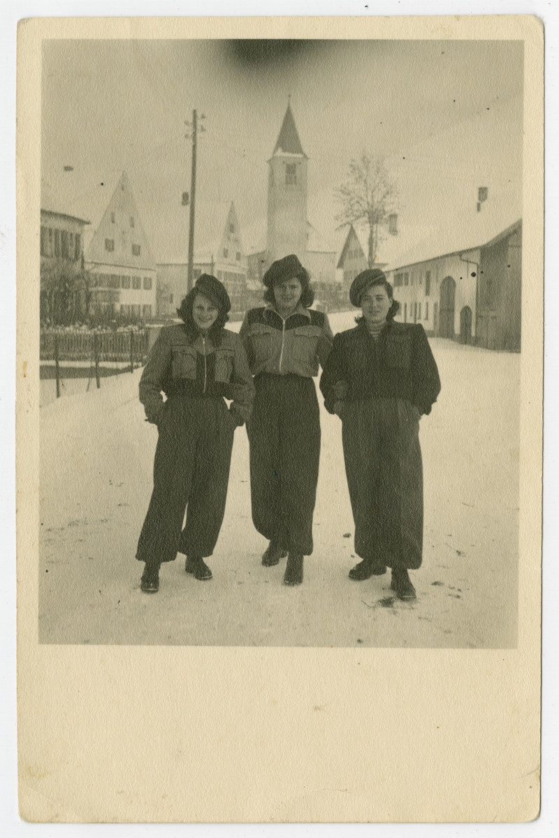 Three young women from the Holzhausen kibbutz hachshara stand on a snowy street.  Rifka Weiss in on the right and her cousin Malka is next to her.