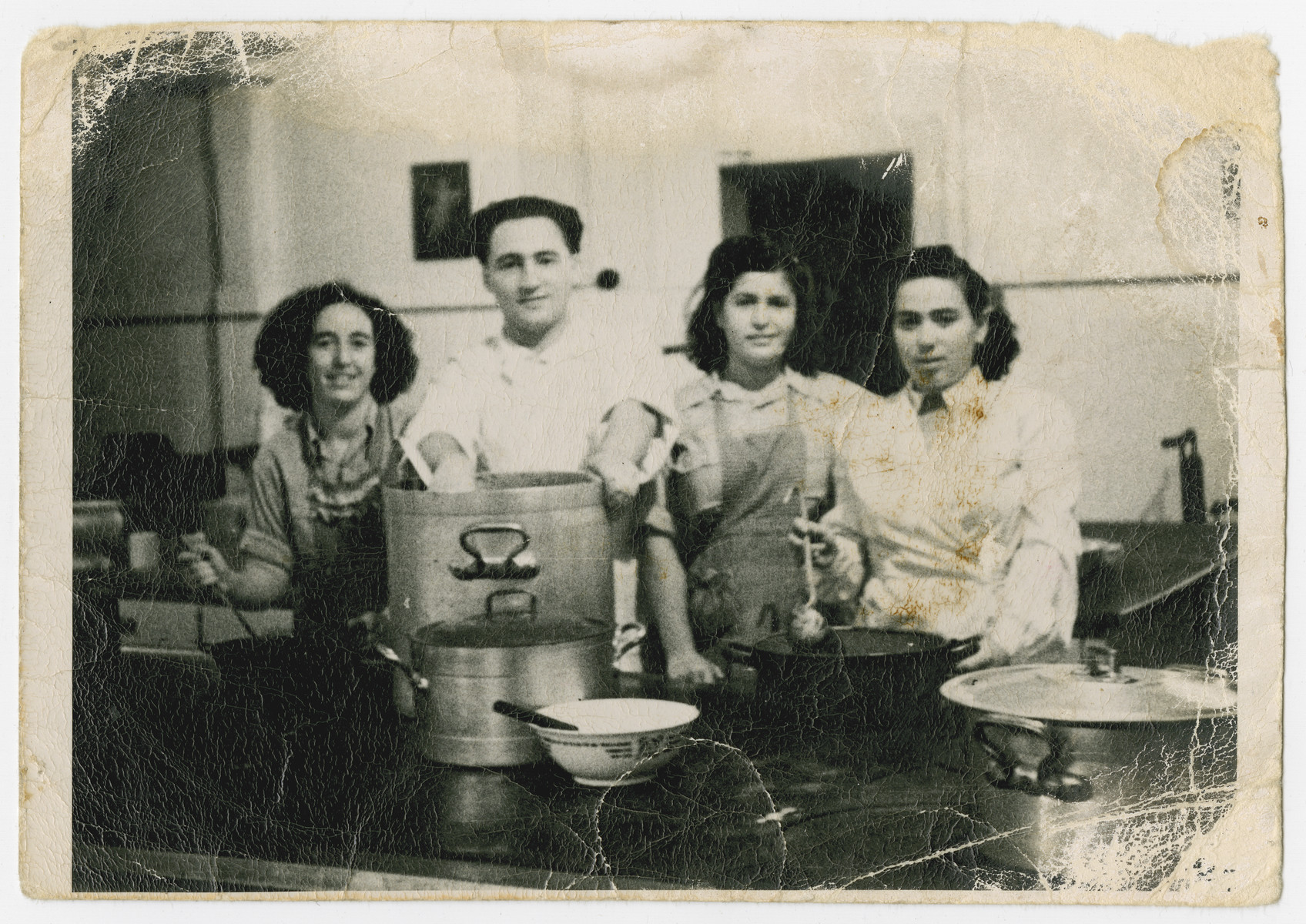 Members of the Holzhausen kibbutz hachshara cook in the camp kitchen.  Rochel is on the left; Rifka Weiss is standing on the right.