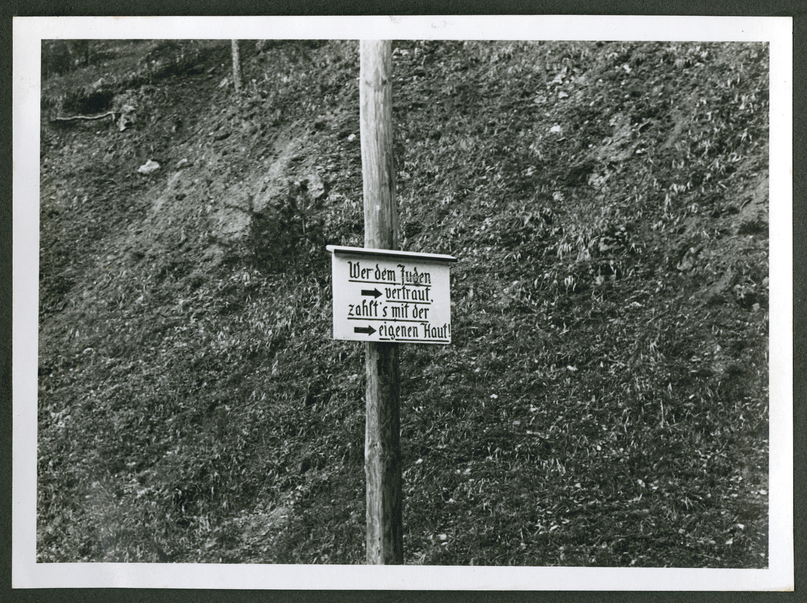 """One photograph from an album of antisemitic signs in Germany.  The sign reads (in German), """"Wer dem Juden vertraut zahlt's mit der eigenen Haut.""""  [He who trusts the Jew pays with his own skin.]"""