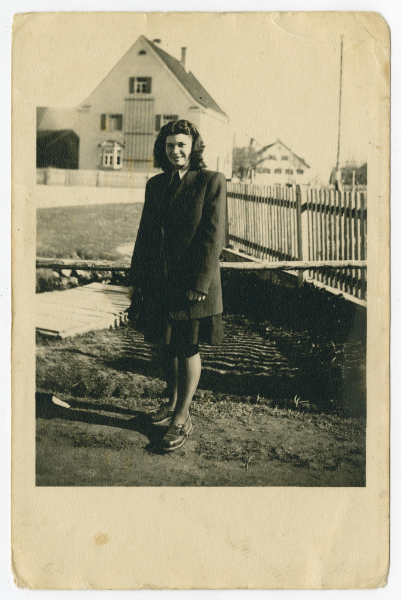 Malka Weiss (cousin of the donor) stands outside next to a fence in the Holzhausen displaced persons camp.