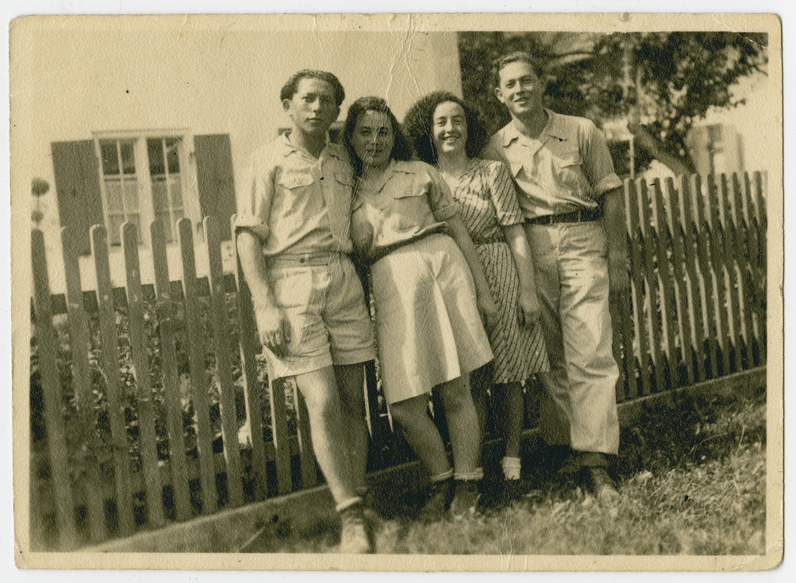 Four young people pose in the Holzhausen kibbutz hachshara.  From left to right are Tzvi, Rifka Weiss and Rochel (Rachel).  The man on the right is not identified.