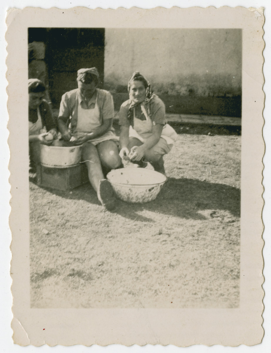 Three young women peel potatoes into large bowls in the Holzhausen displaced persons camp.
