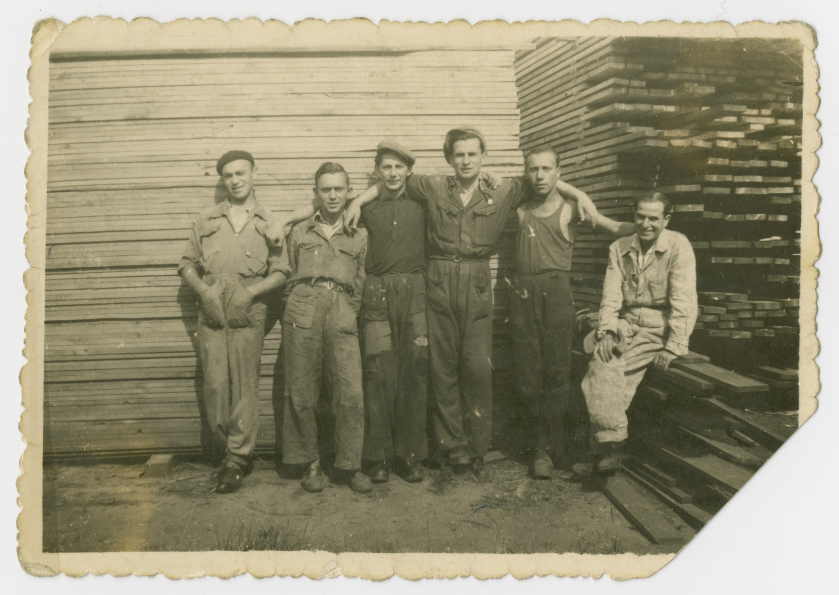 Polish Jewish men pose at a lumberyard [probably in prewar Poland] .  Those pictured include Tadeuz and Adolf Kleiman.