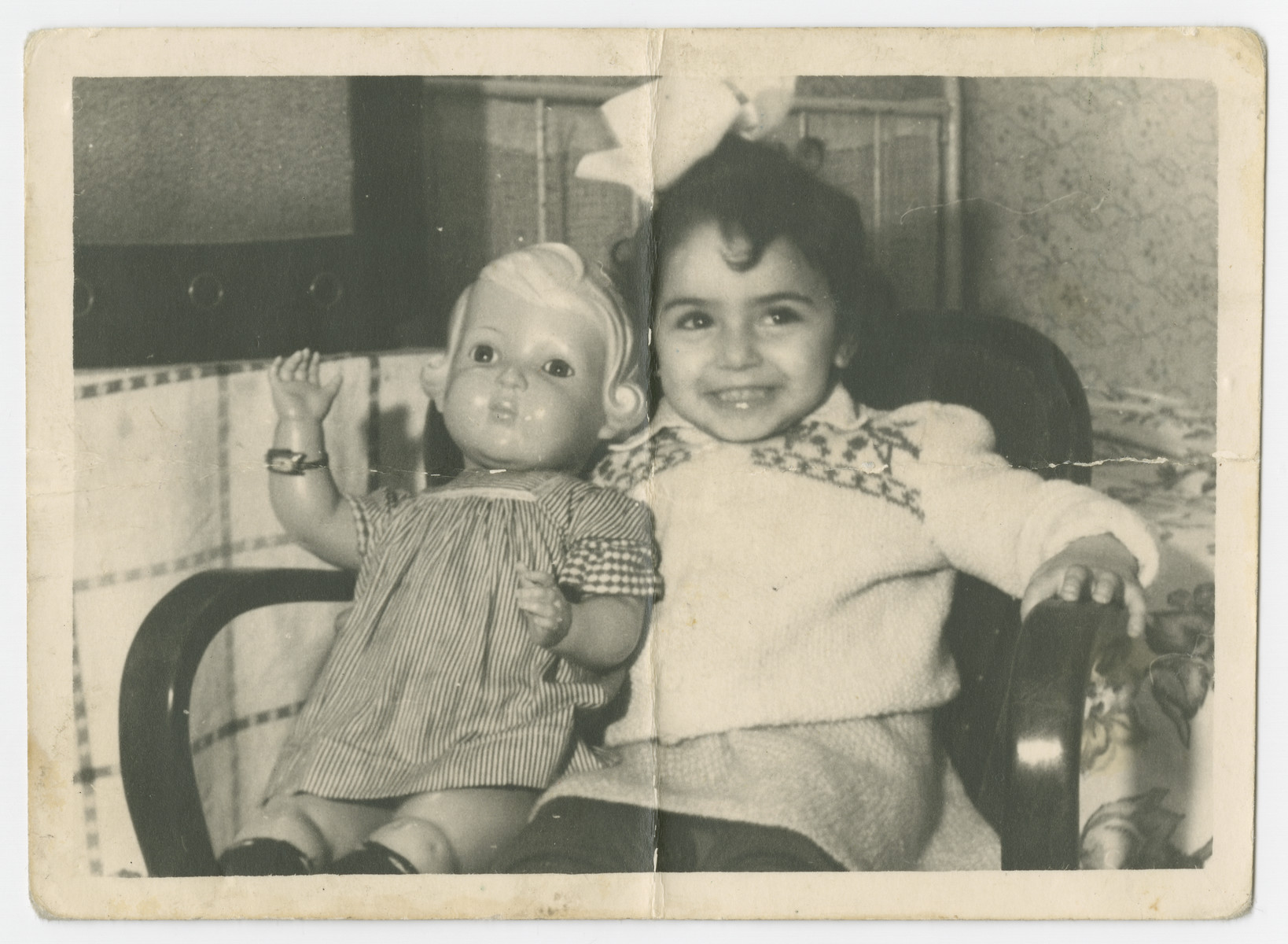 Ellen Zinger (daughter of Malka Lubochinski and Abram Zinger) sits in an armchair with her doll in the Bergen-Belsen displaced persons camp.