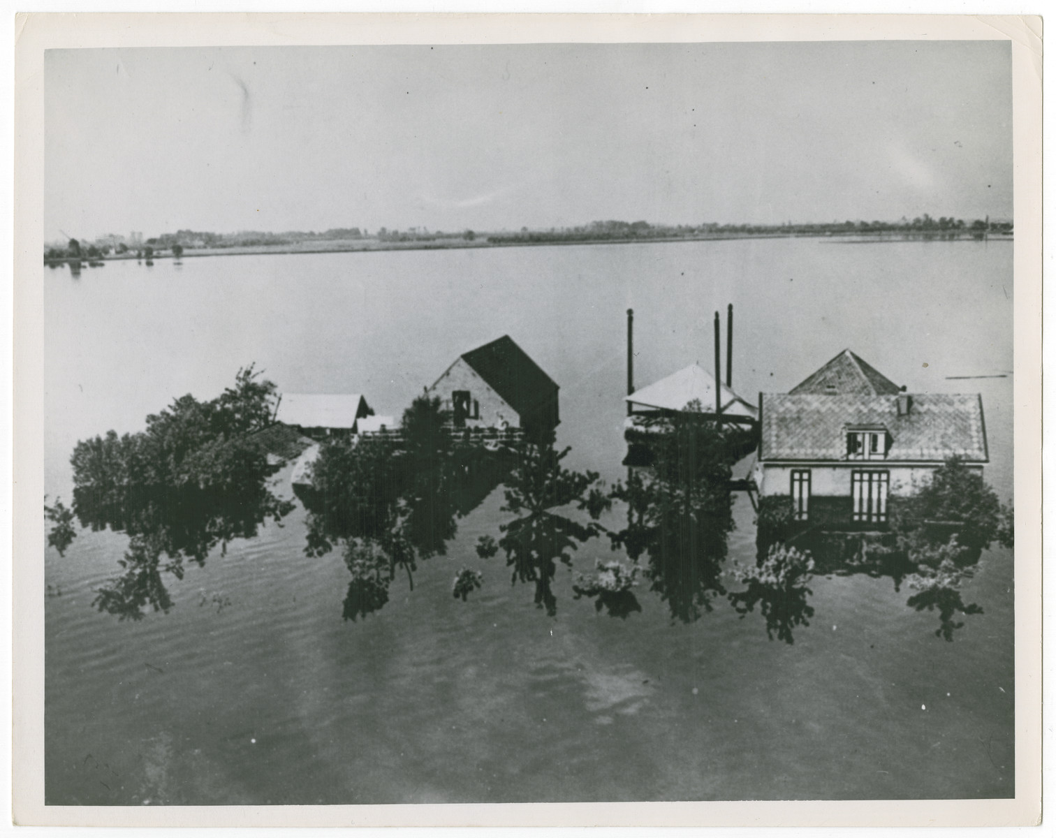 "An aerial view of flooded areas around the small town of Oud-Loosdrecht, Holland.  Original caption reads:  ""Twelve hundred persons died of starvation in Amsterdam, Holland, when the Germans destroyed the country's dikes and flooded Dutch farms with sea water.  Before the Allies liberated the Low Countries, American Military authorities sent more than 2150 B-17 Flying Fortresses to drop 2500 tons of food to the starving population.  When the Germans were pushed back land vehicles and ships rushed food to Holland reducing and finally checking the deaths.  This is an airview of flooded areas around the small town of Oud-Loosdrecht, Holland""."