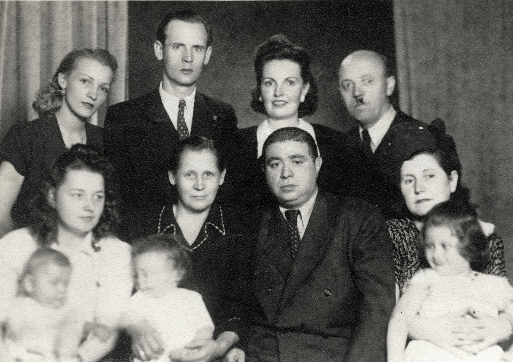 Group portrait of the Ecksteins (a Slovak Jewish family), with the Pajanko family, the Slovak family who hid their daughter.  Jonas Eckstein is seated second from the right.  Gerta Eckstein is sitting on her mother's lap on the far right.  Maja Pajanko is seated on the far left.  Mrs. Pajanko is in the center and Mr. Pajanko is standing behind Valerie Eckstein.
