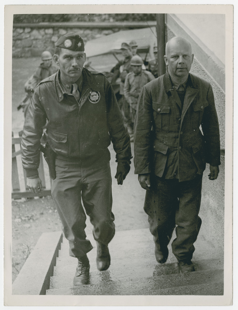 "SS General Karl Albrecht Oberg (right), known as the ""Butcher of Paris"" because of his activities as Nazi police leader in France, is shown with U.S. Major Cecil Simmons, who captured him May 26, 1945, in the mountains near Kitzbuhel, Austria.  Original caption reads:  ""SS General Karl Albrecht Oberg (right), known as the ""Butcher of Paris"" because of his activities as Nazi police leader in France, is shown with U.S. Major Cecil Simmons, who captured him May 26, 1945, in the mountains near Kitzbuhel, Austria. Oberg, disguised as a private in the Austrian Army, was recognized by Major Simmons, who remembered his peculiar egg-shaped head.  The Nazi organized the German office which dealt with resistance movements in France, and he conferred frequently with Abeth, Doriot and Laval.  He blames Stulpnagel, his immediate superiror, for the many executions he carried out in Paris.  When captured, his hideout contained a hoard of food sufficient to last for two years""."