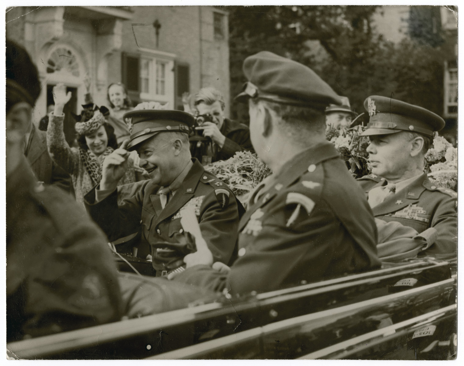 """Gen. Eisenhower pays an official visit to The Netherlands after liberation.  Original caption reads:  General Eisenhower's visit to The Netherlands.  General Eisenhower leaving U.S. Ambassador Hornbeck's residence at the Hague.  In car Ike, Col. Griffith (with back to camera) and Lt. Gen. W.B.Smith.  (Girl waving immediately in front of General Eisenhower was girl who gave the General flowers and a kiss just before the General got in the car""""."""