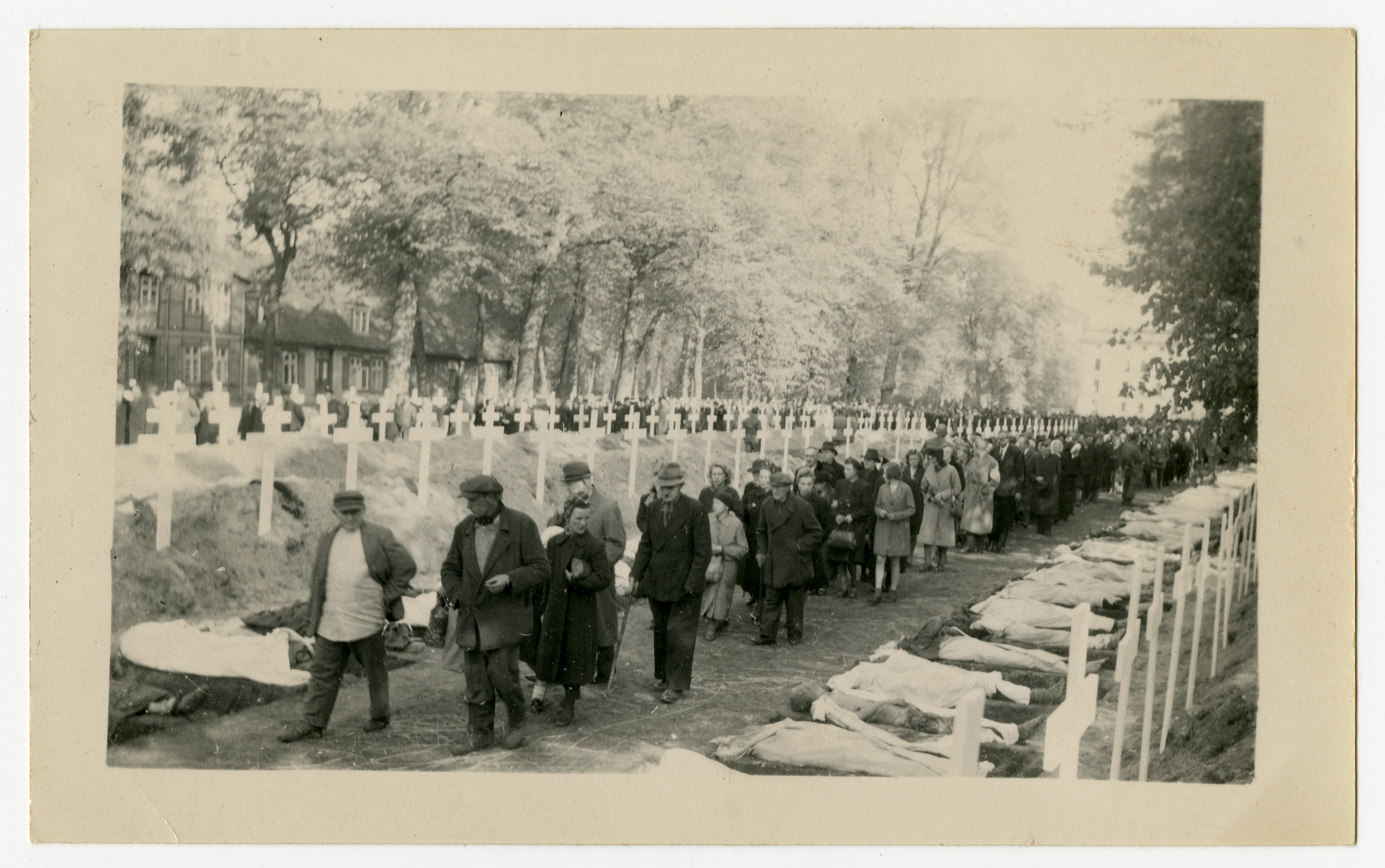 The population of Ludwigslust is forced to walk past the bodies of concentration camp victims prior to their reburial on the palace grounds of the Archduke of Mecklenburg.