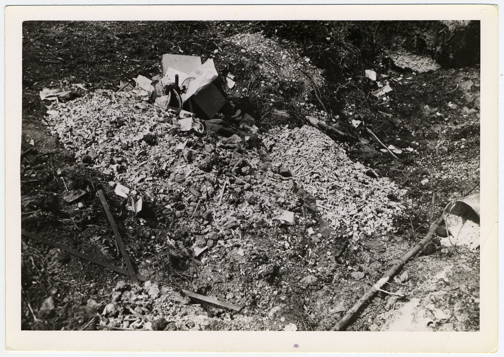 "Human remains of prisoners found near the crematorium at the Dachau concentration camp.  Original caption reads, ""Bone pile outside the crematory at the Dachau concentration camp. In the past 2 or 3 months, the inmates claim that almost 15,000 people have been cremated."""