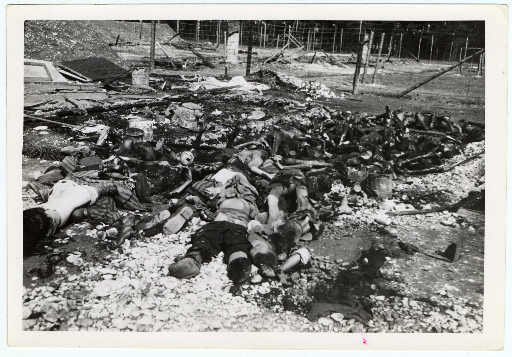 "The bodies of burned prisoners lie in the rubble of the barracks at Landsberg.  Original caption reads, ""Pile of bodies which will be carried by German civilians from the town of Landsberg, Germany, and buried in graves also dug by German civilians in Stalag #4 Concentration Camp at Landsberg. These are the bodies of political prisoners, starved and burned to death by S.S. troops at the prison."""