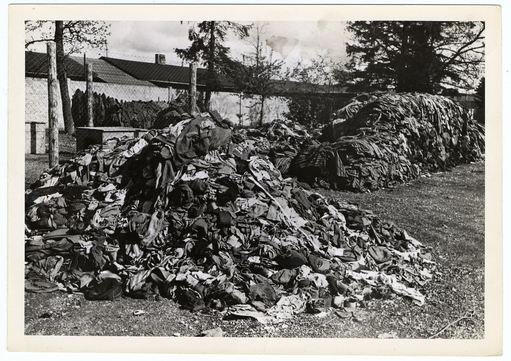 "Pile of prisoners clothing found near the crematorium in the Dachau concentration camp.   Original caption reads, ""Dachau Atrocity Camp: Tattered clothes from prisoners who were forced to strip before they were killed, lay in huge piles in the infamous Dachau concentration camp which was liberated by the 7th U.S. Army troops. Clothing was reused because of material shortages."""