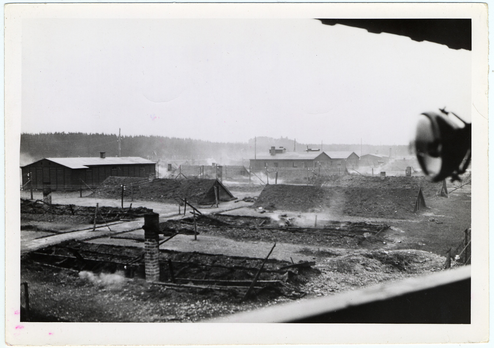 """View of the still smoldering barracks at the Landsberg (Kaufering Lager I) sub-camp of Dachau concentration camp.  Original caption reads, """"Landsberg Atrocity: The emaciated bodies of victims of German cruelty at Landsberg prison. Before retreating in the face of the 7th Army attack, guards locked the Jewish prisoners in their huts and told them they would be shot if they came out. Then the buildings were set on fire. Some burned to death in their huts, others found strength to break down the doors and crawl out to die in the streets. Most prisoners were naked, some had remnants of clothing on their charred bodies. View of the prison camp showing the cahrred remains of the burned huts in the foreground."""""""