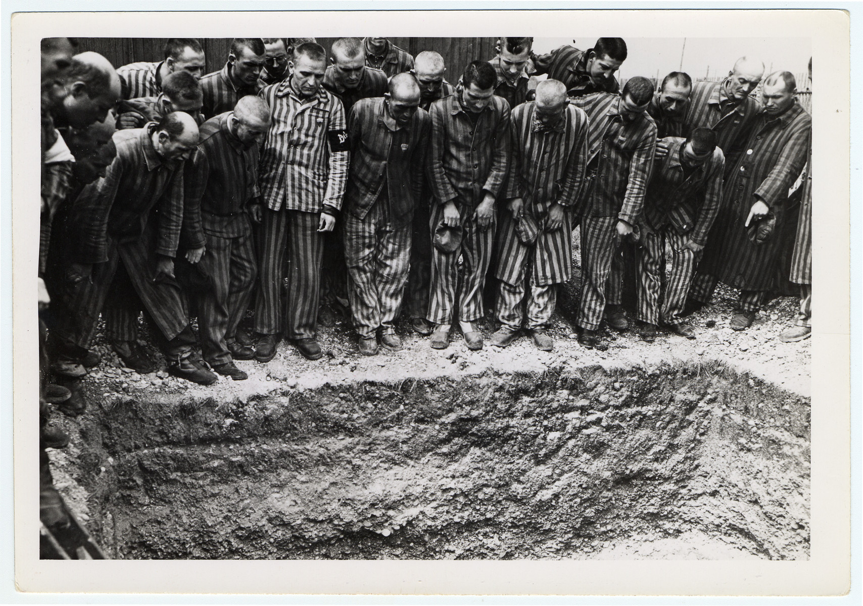 """Newly liberated prisoners stand around a mass grave at Dachau concentration camp.  Original caption reads, """"The prisoners show where they buried some of the comrades everyday, the ones who could not withstand the cruel treatment and starvation diet handed out by their German keepers. Feet and partially covered head protrude from under the dirt in this mass burial pit."""""""