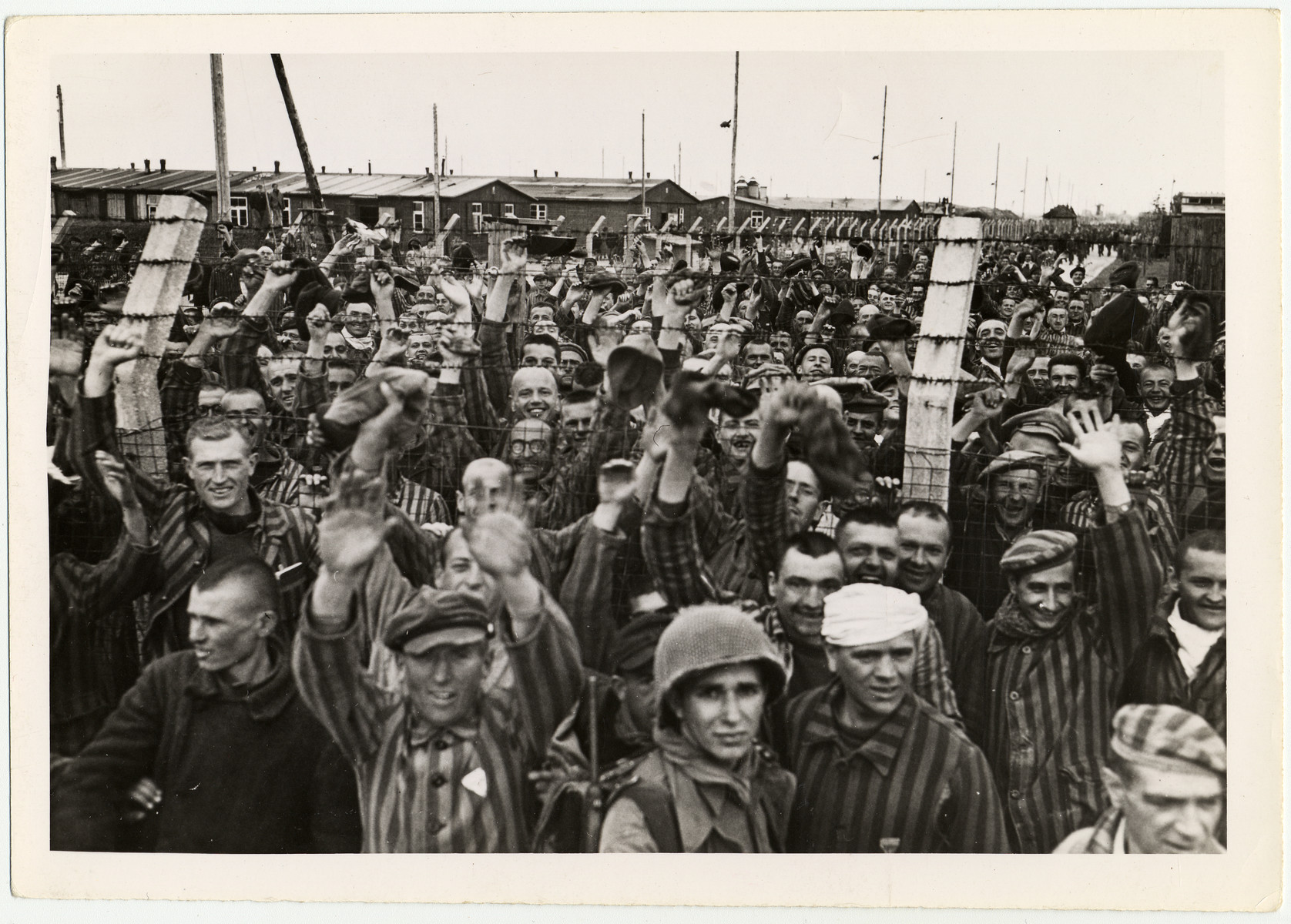 "Liberated prisoners greet American soldiers at Allach, a sub-camp of Dachau.  Original caption reads, ""In prison stockade at Dachau, prisoners cheer the liberating Americans, who freed them from the inhuman treatment of the S.S. Gaurds."""