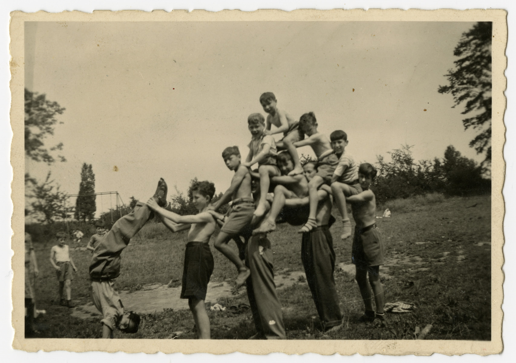 Jewish orphans in Home de la-Bas in Aische-en-Refail build a human pyramid.  George Sylin is holding one counselor's feet and Hans is in the rear. Charles Rojer in the center squashed down and beginning to slide through the arms of the rear support counselor.