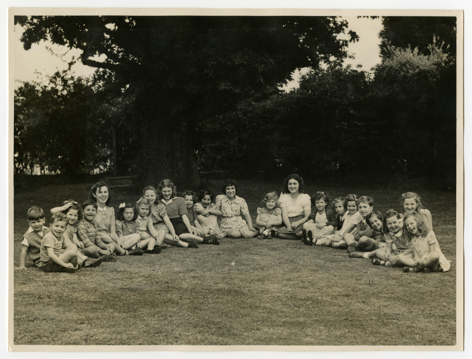 Child survivors sit outside in a semi-circle in the Weir Courtney children's home.
