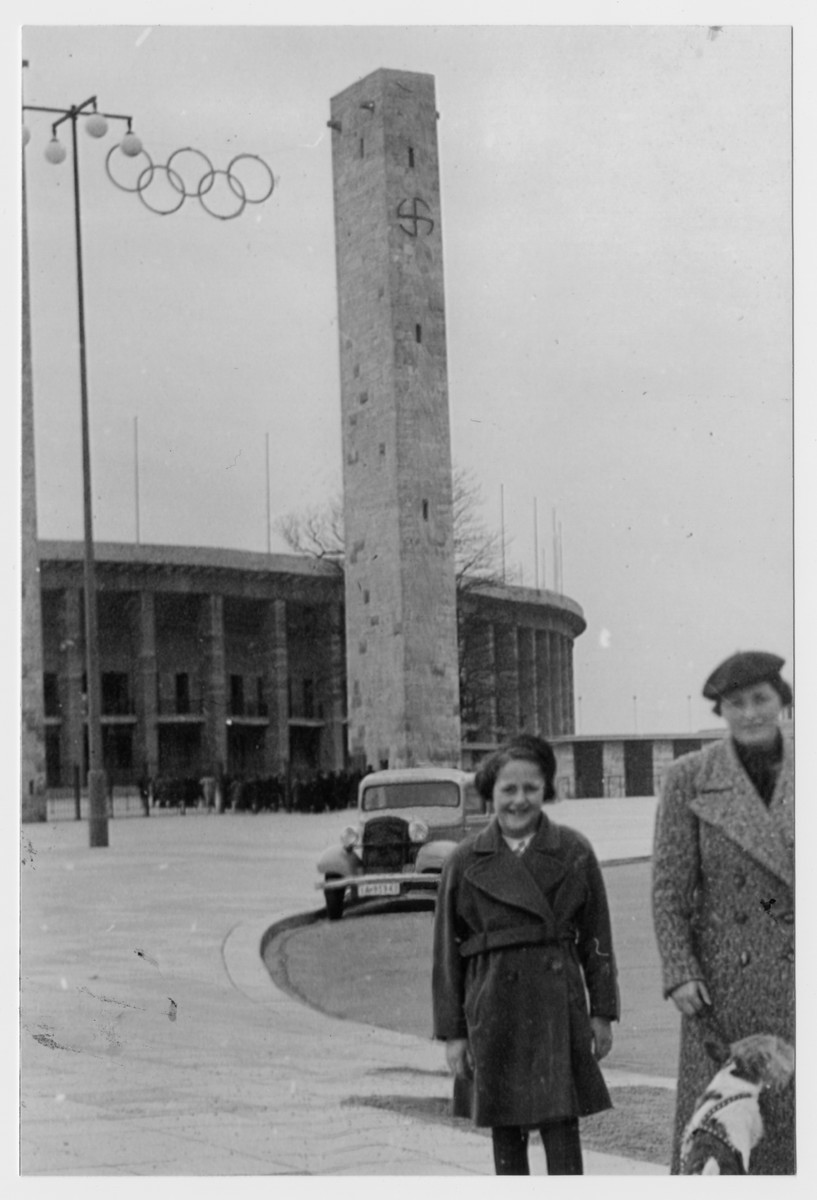 Anne Forchheimer visits her aunt Greta Sichel Forchheimer in Berlin in the autumn following the Olympics.   A pole with the Olympic rings stands behind them as well as a tower with a swastika.