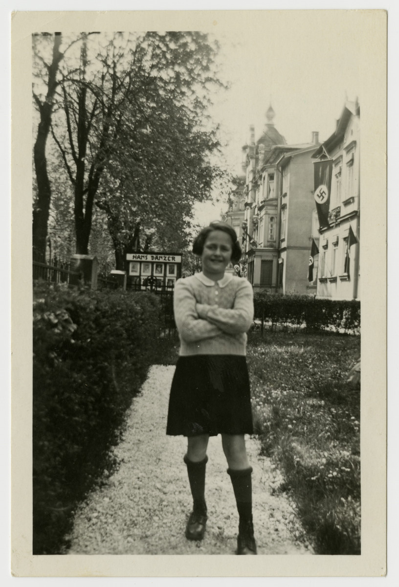 Anne Forchheimer, a Jewish child in Coburg, Germany, poses in front of a large building bedecked with a Nazi flag.