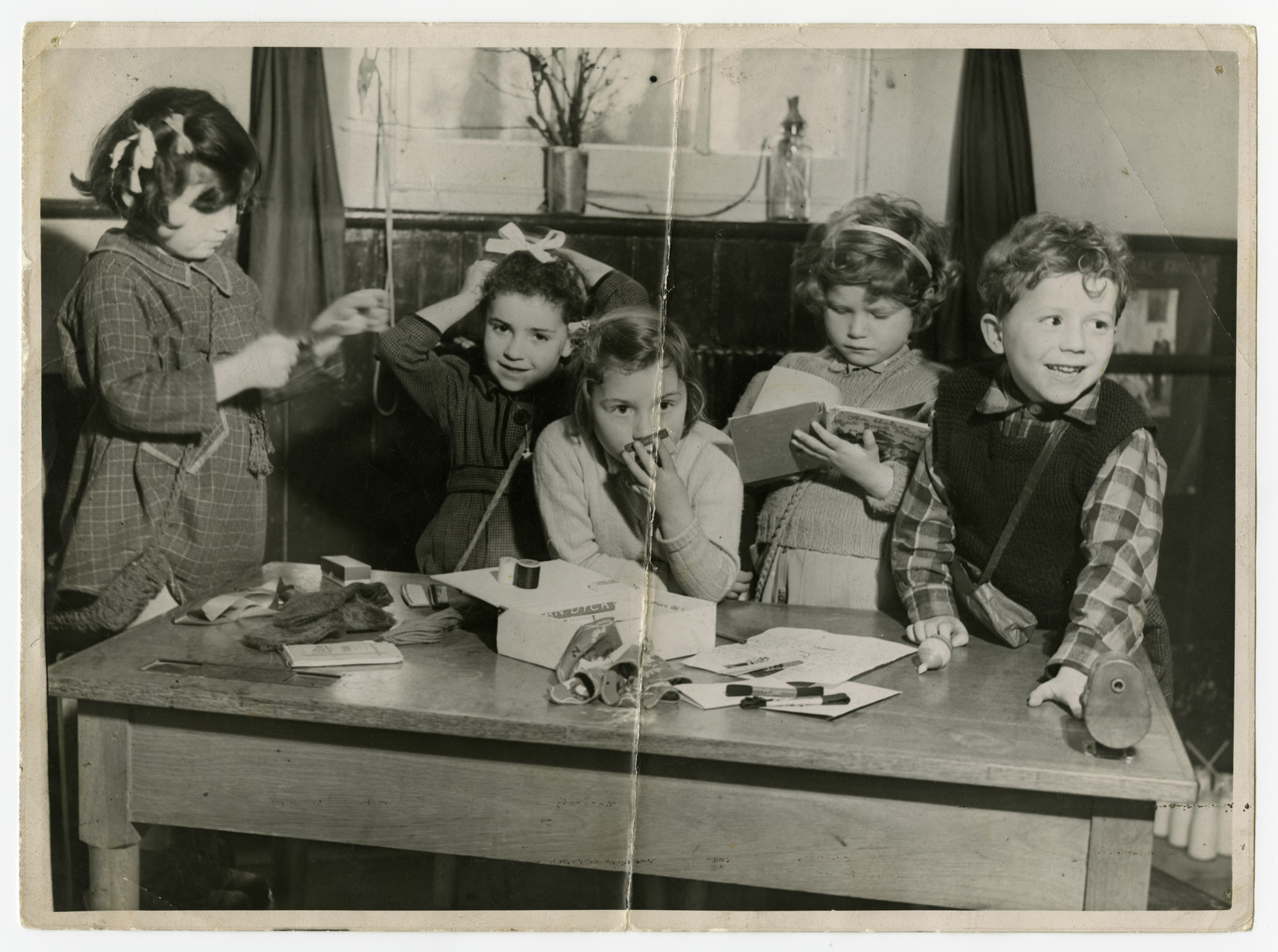 Young children in the Weir Courtney children's home gather by a table with art and sewing supplies.  From left to right are unidentified, Zdenka Husserl, Tanja Muench, Letzi Sonnenschein, and Denny Muench.