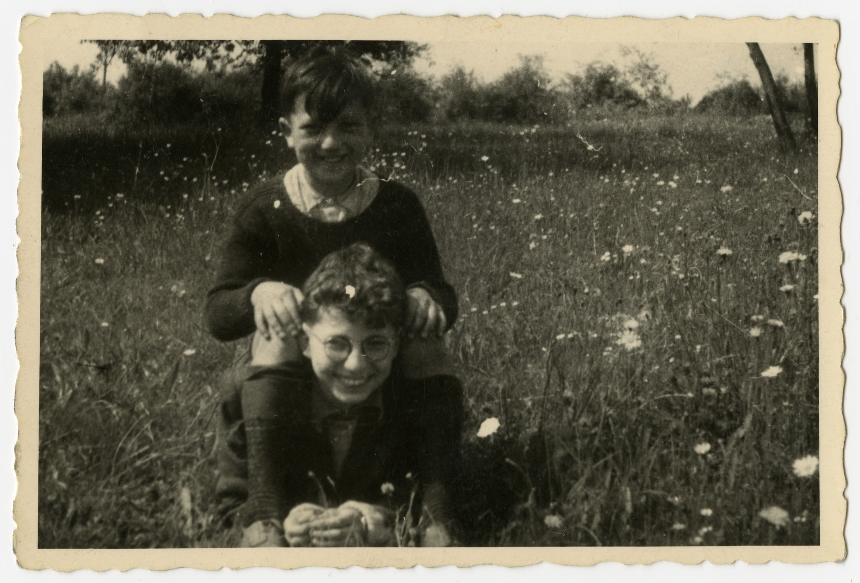 Close-up portrait of boys lying in the grass outside Home de la-Bas in Aische-en-Refail.  George Sylin, the son of the director of the Home de La-Bas, is on the bottom, and Charles Rojer is seated on top of him.
