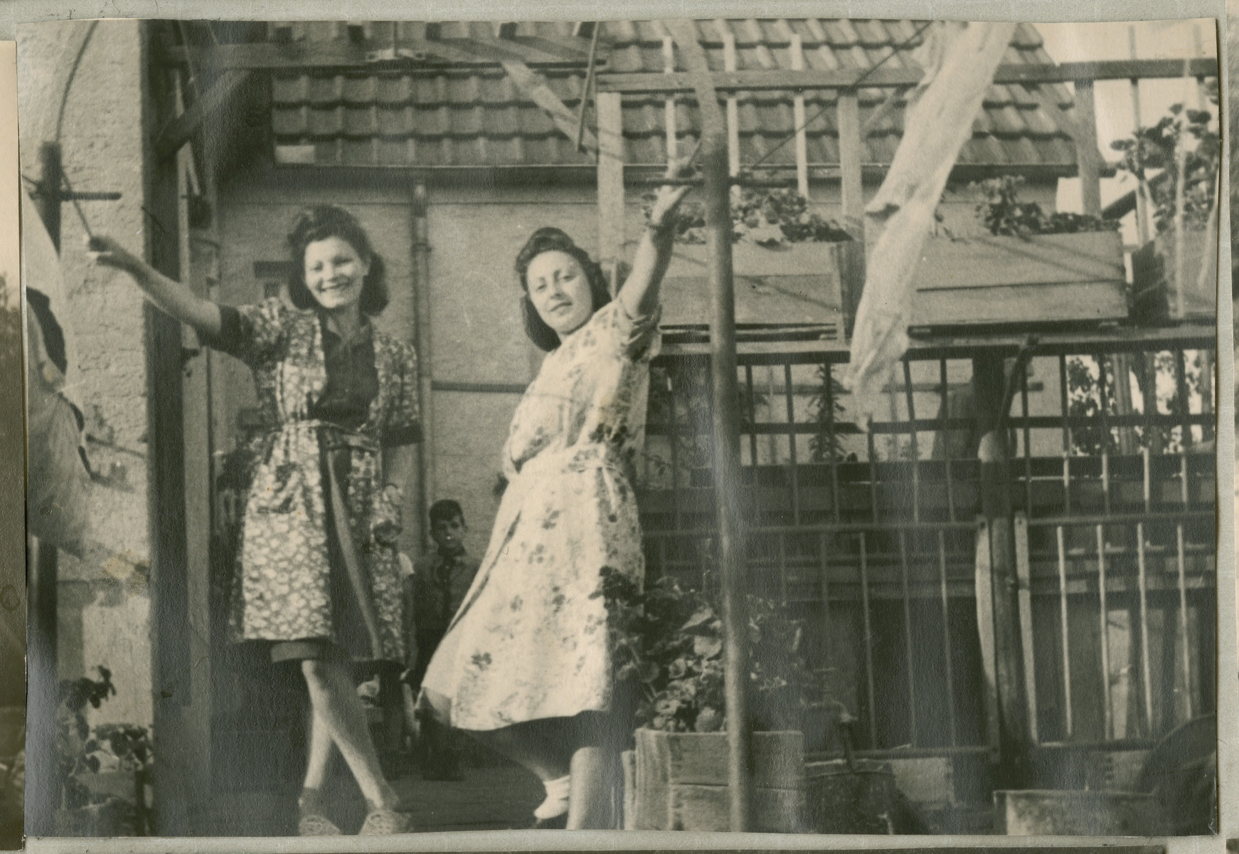 Hanna Bratman and her sister-in-law Hanka Bratman Fisch stand outside a house in the Lampertheim displaced person camp.
