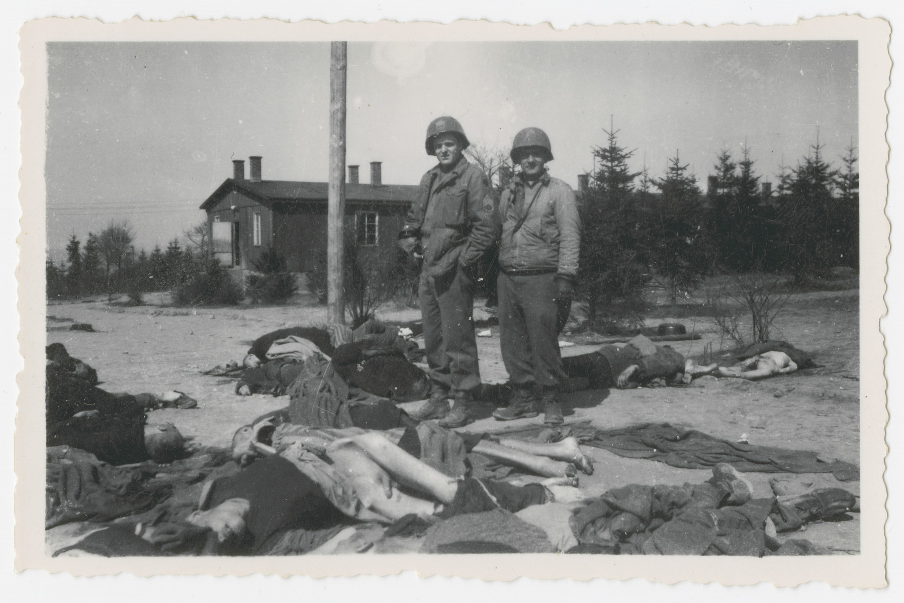 Two American soldiers look victims' corpses lying in an open field in the Ohrdruf concentration camp.