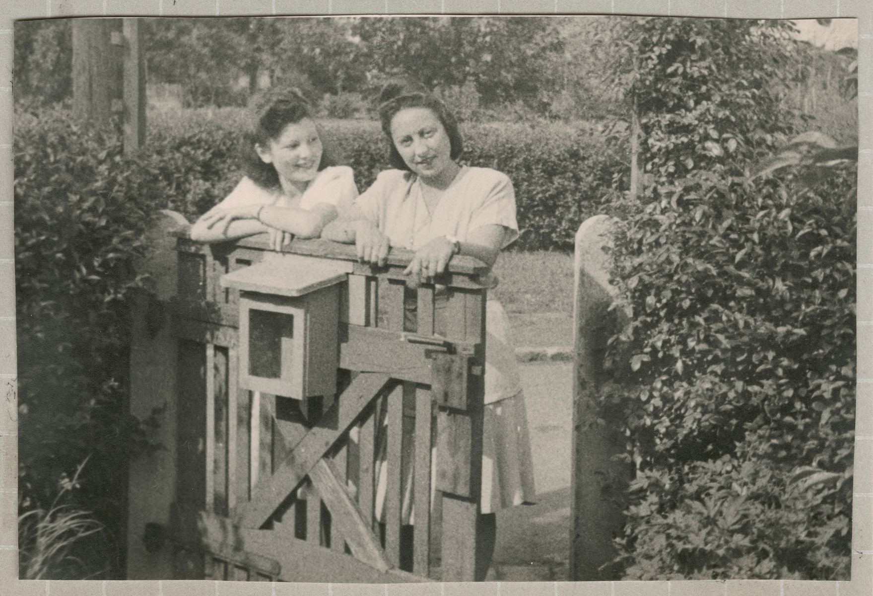 Hanna Bratman and Hanka Bratman Fisch stand by a gate in the Lampertheim displaced persons camp.