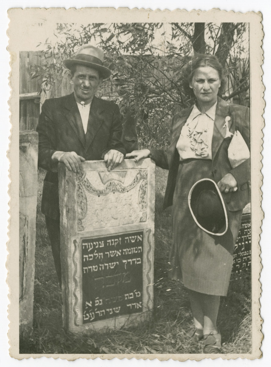 Two family members pose next to the grave of Malka, the daughter of Moshe, a member of the Kodzidlo or Herszlikowicz family.   Pictured are probably Gussie and Srul, an uncle of Hanna.