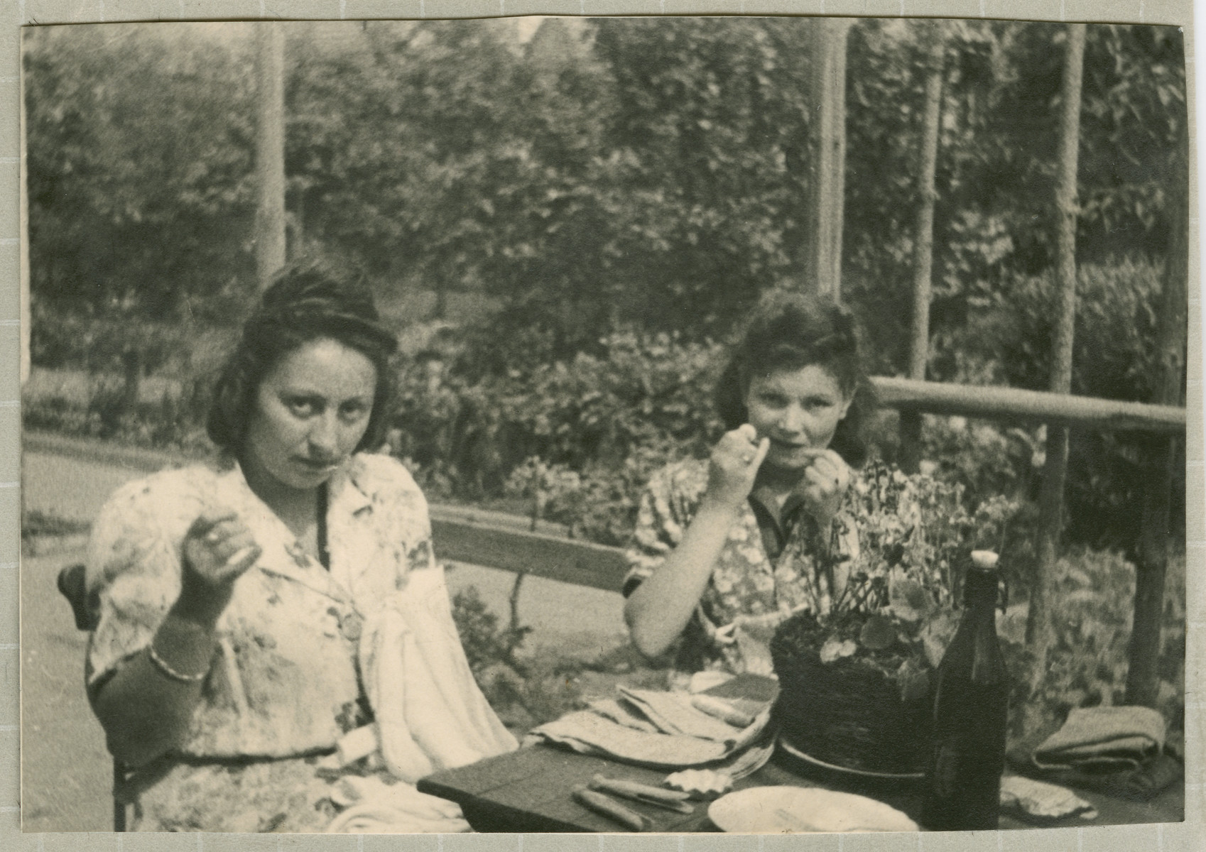 Hanna Bratman and her sister-in-law Hanka Bratman Fisch sit outside and sew in the Lampertheim displaced persons camp.