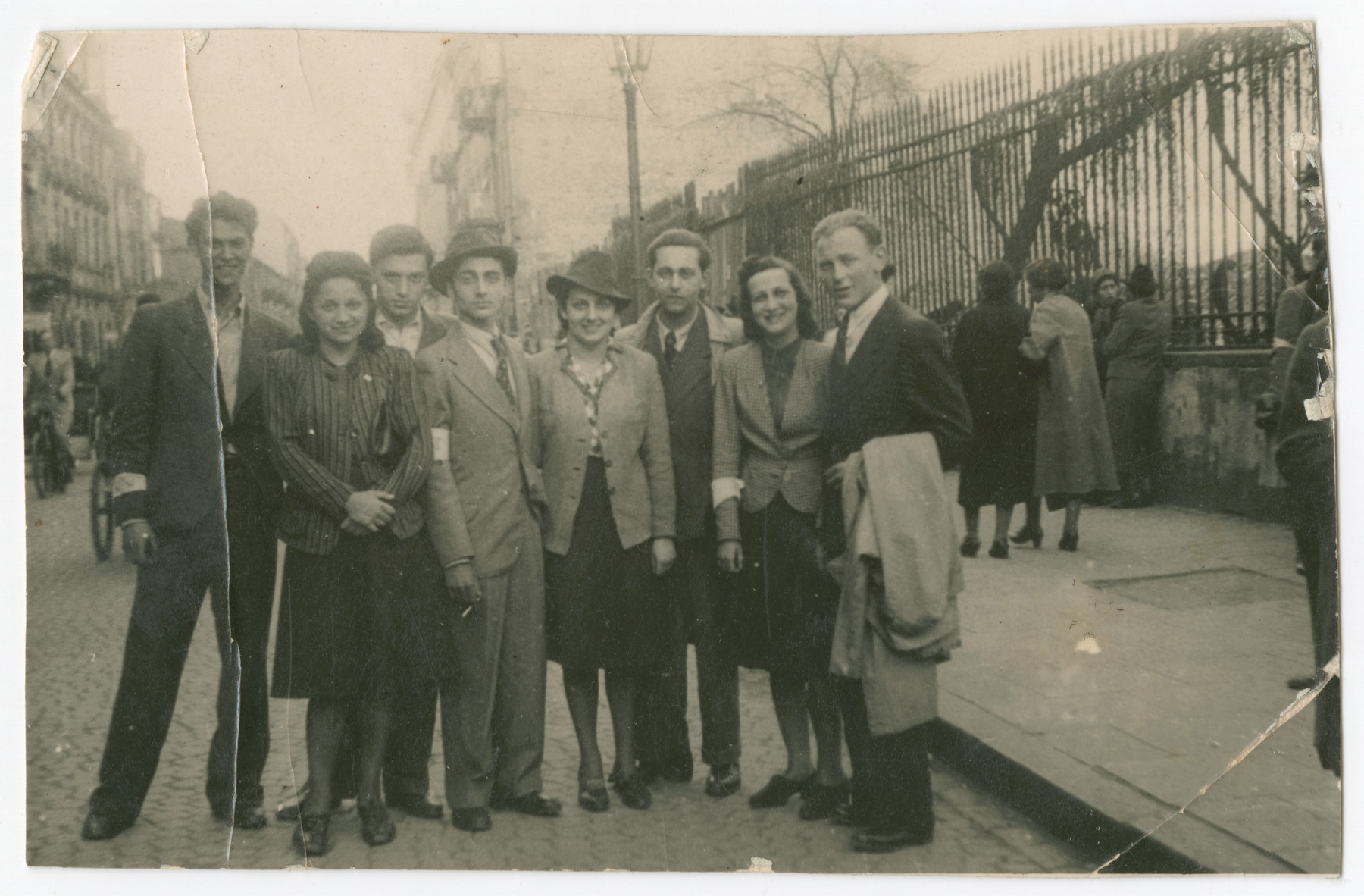 A group of Jewish young adults pose on a street in Warsaw.  Mary Wattenberg Berg) is standing second from the left.  Behind her to the right is her boyfriend Romek Kowalski.