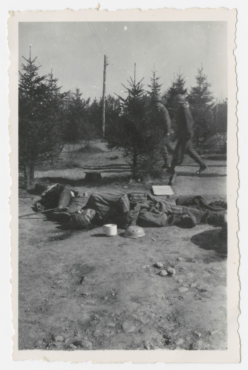Two American soldiers lwalk by victims' corpses lying in an open field in the Ohrdruf concentration camp.