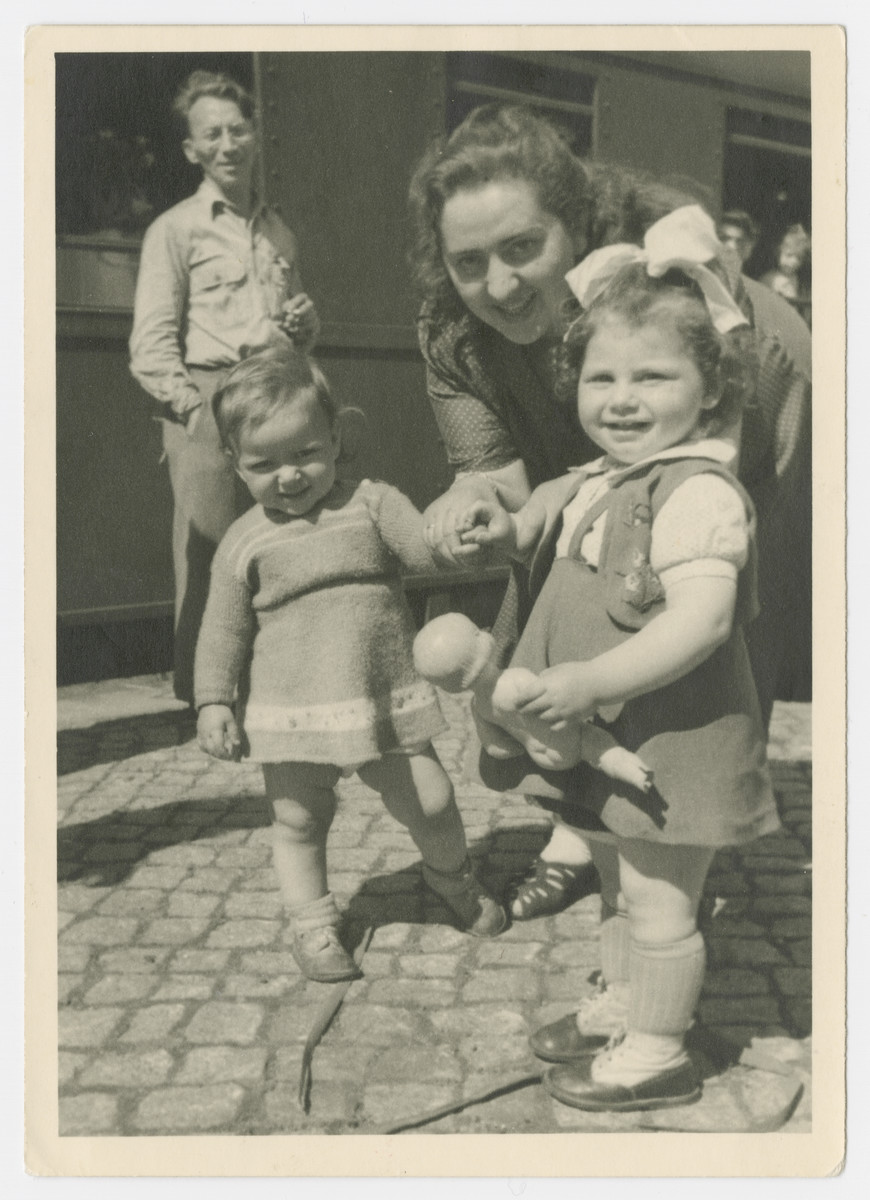 An unidentified woman poses with two toddlers in or near the Bergen-Belsen displaced persons camp.
